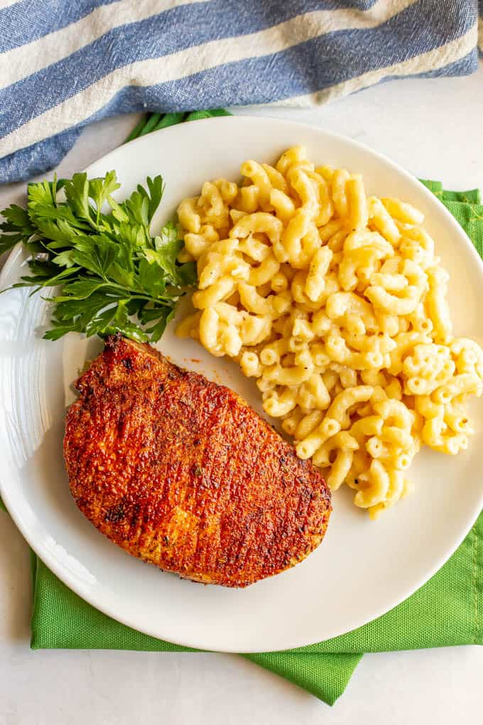 Seasoned and cooked air fryer pork chops served on a plate with mac and cheese