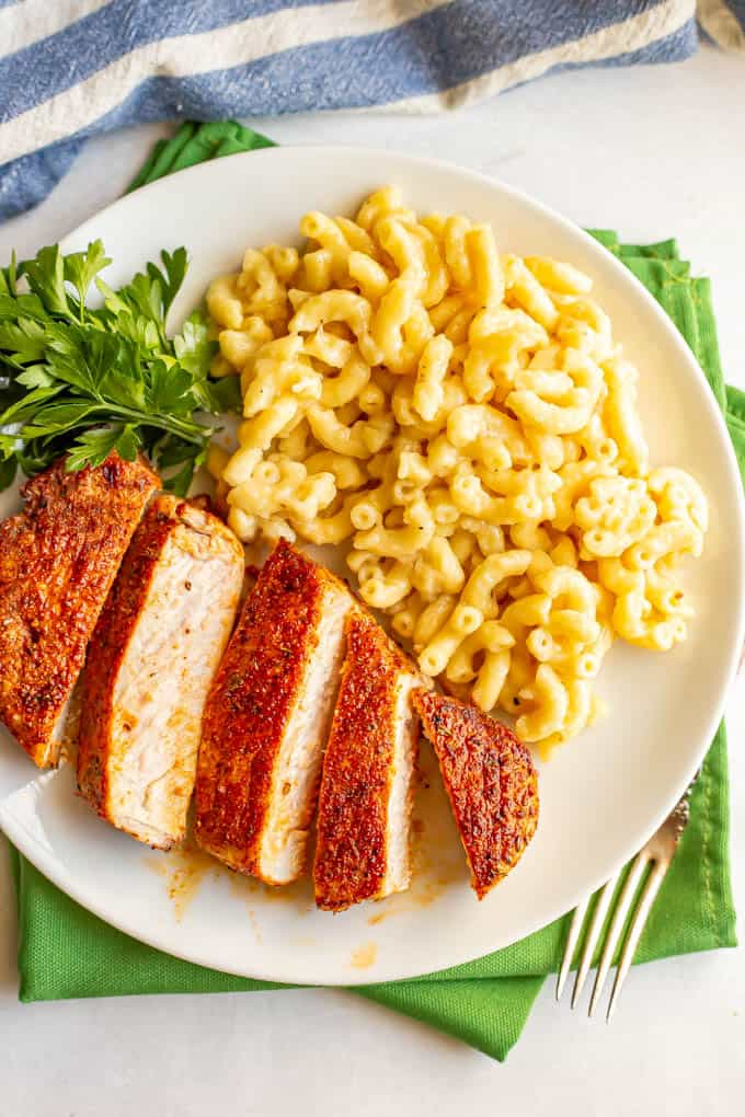 Seasoned cooked pork chops sliced and served with macaroni and cheese on a white plate on top of green napkins
