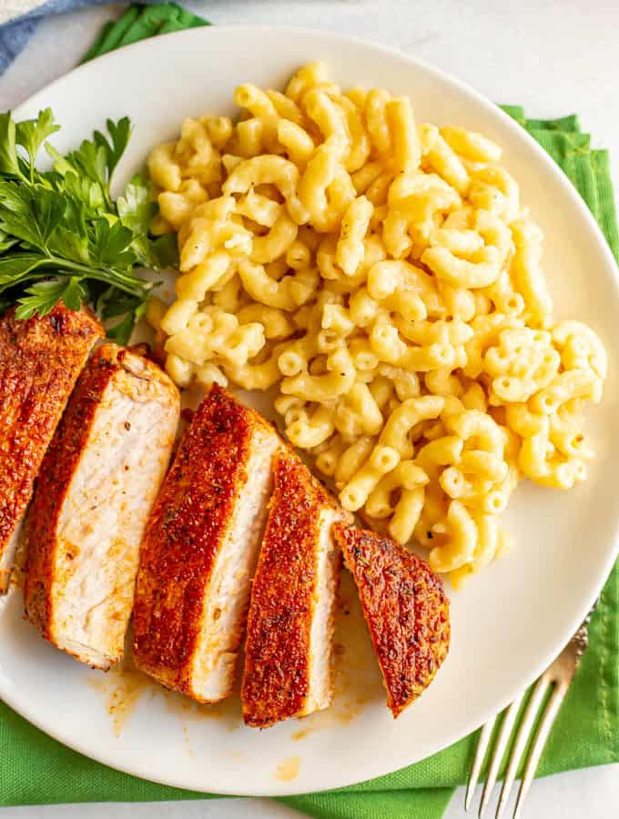 Seasoned cooked pork chops sliced and served with macaroni and cheese