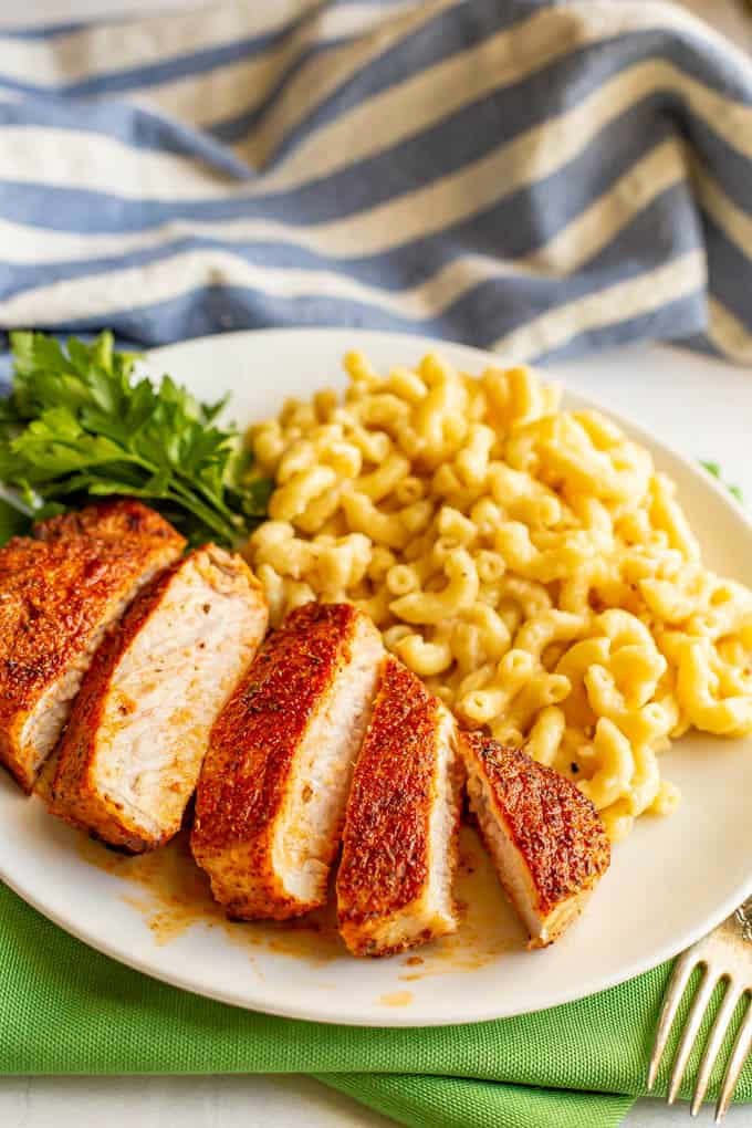 Thickly sliced pork chops served on a white plate with mac and cheese