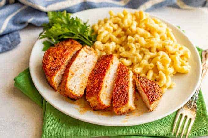 Sliced seasoned pork chop served on a white plate with mac and cheese and a parsley garnish