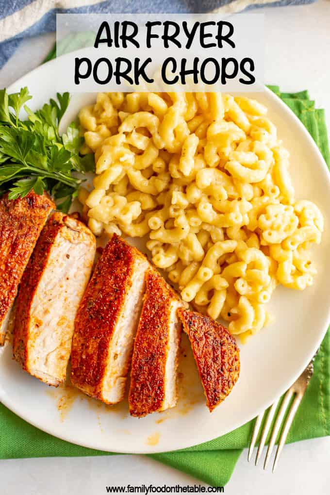 Sliced seasoned pork chop served on a plate with mac and cheese and a text box overlay
