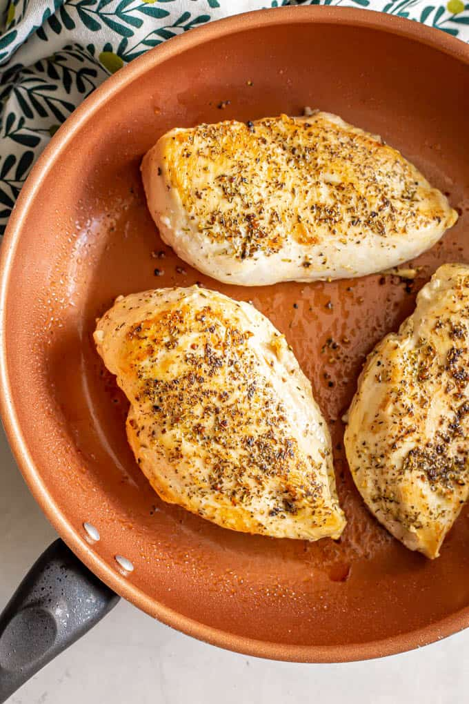 Seasoned and seared chicken breasts in a sauté pan