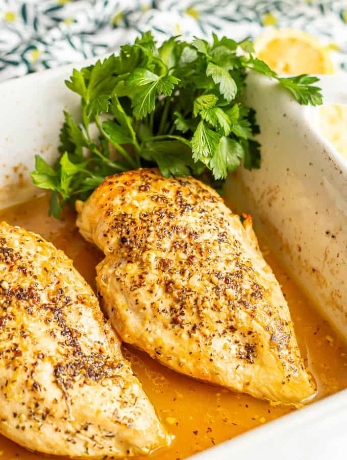 Seared and baked chicken breasts in a lemon sauce in a casserole dish