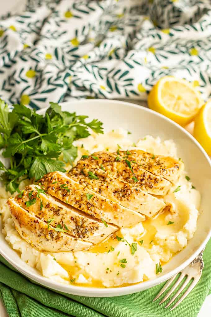 Sliced lemon chicken served over mashed potatoes in a large white bowl with a lemon butter sauce and parsley over top