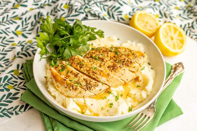 Sliced lemon chicken served over mashed potatoes in a large bowl with a lemon butter sauce and parsley over top