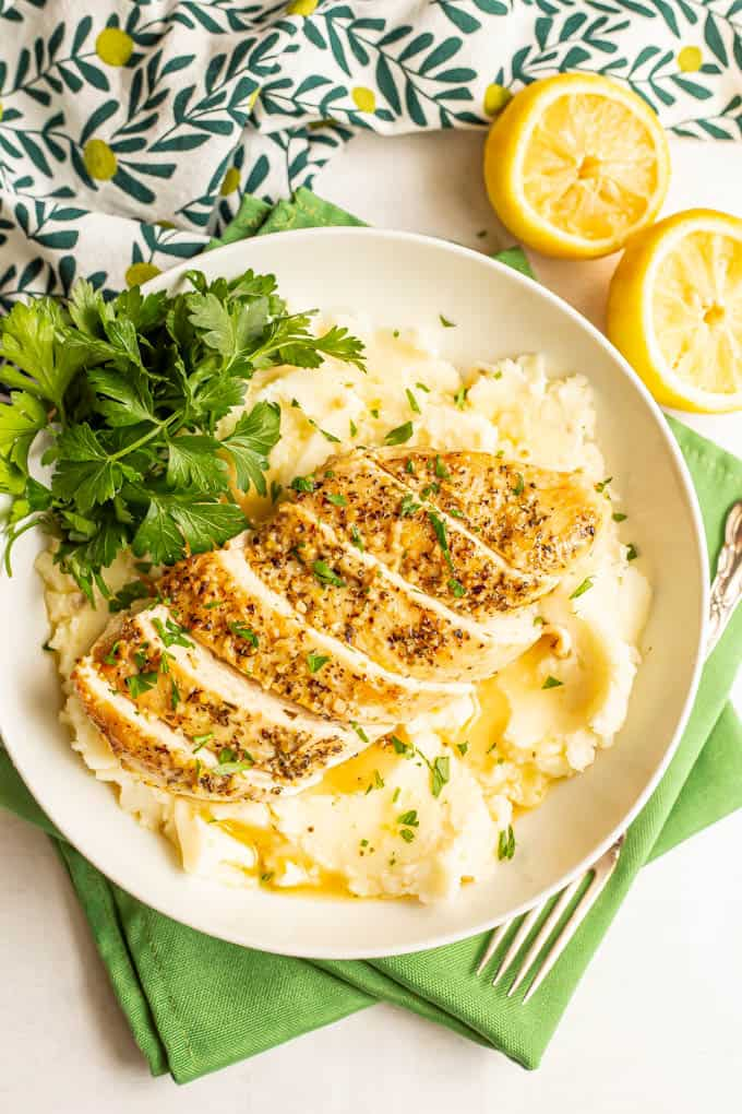 Sliced lemon chicken served over mashed potatoes with a lemon butter sauce and parsley