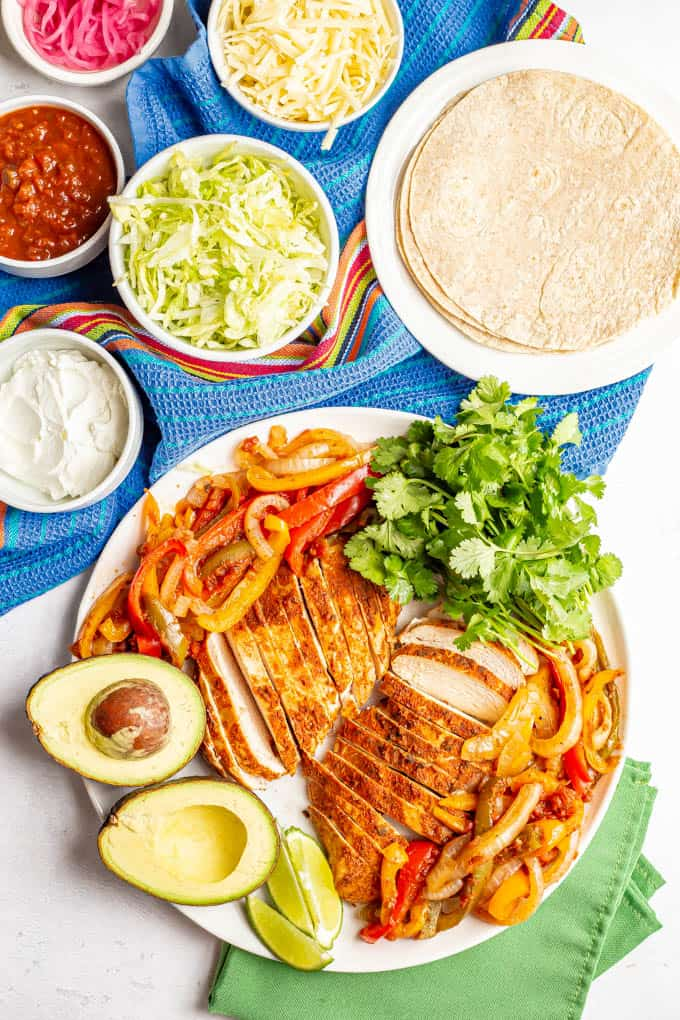 A large white serving platter piled with slow cooker chicken fajitas plus garnishes and bowls of toppings nearby
