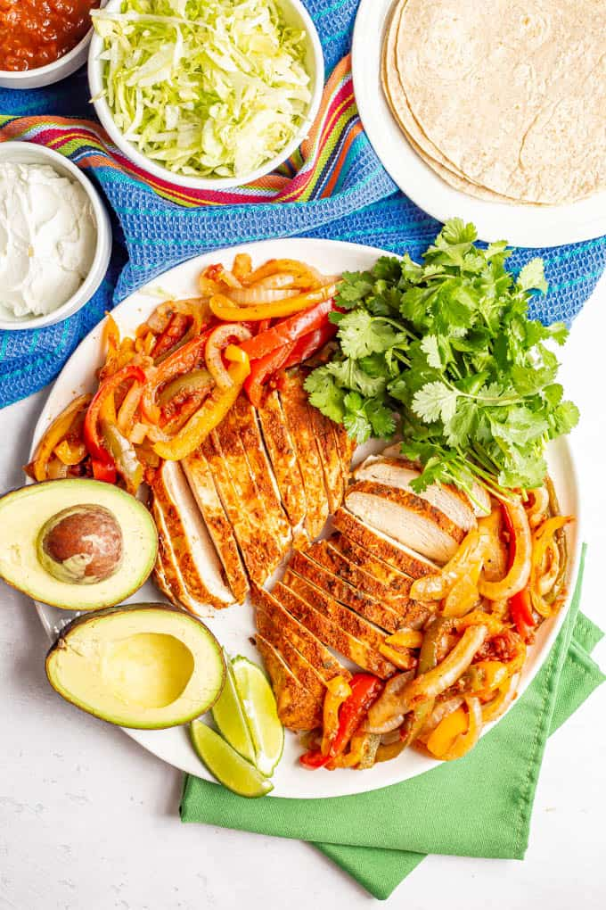 A large white serving platter piled with crock pot chicken fajitas plus garnishes and bowls of toppings nearby