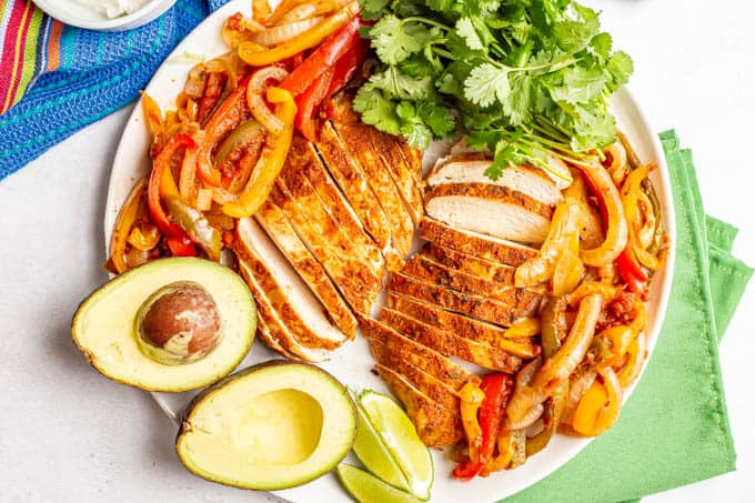 A large white serving platter piled with fajita chicken and peppers and onions, plus garnishes