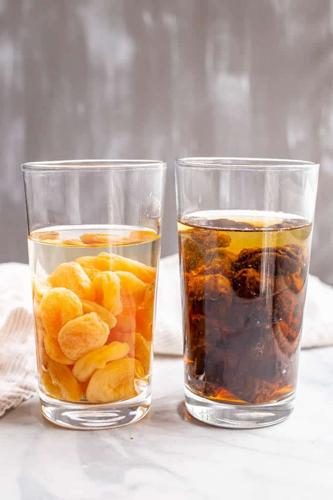 Dried apricots and prunes soaking in water in glasses
