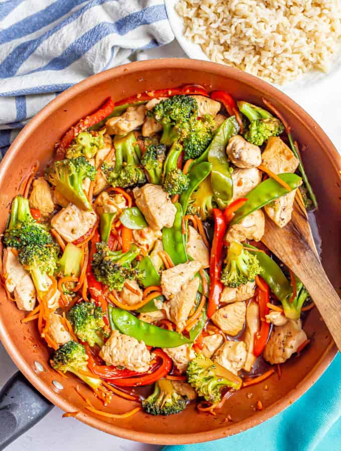 Honey garlic chicken stir fry with colorful vegetables in a large copper skillet with a bowl of rice nearby