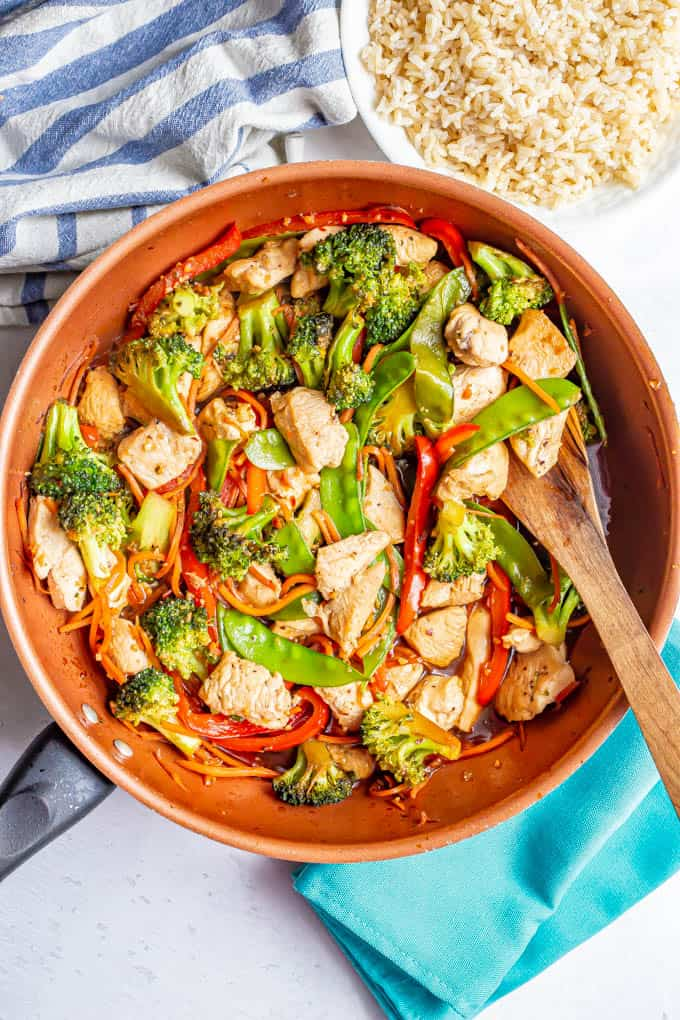 Chicken vegetable stir fry with honey garlic sauce about to be served from a large skillet with a bowl of rice nearby
