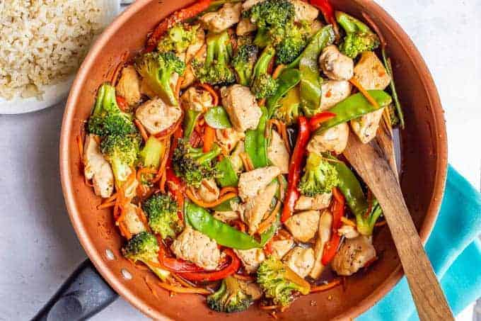Chicken vegetable stir fry with honey garlic sauce about to be served from a large skillet