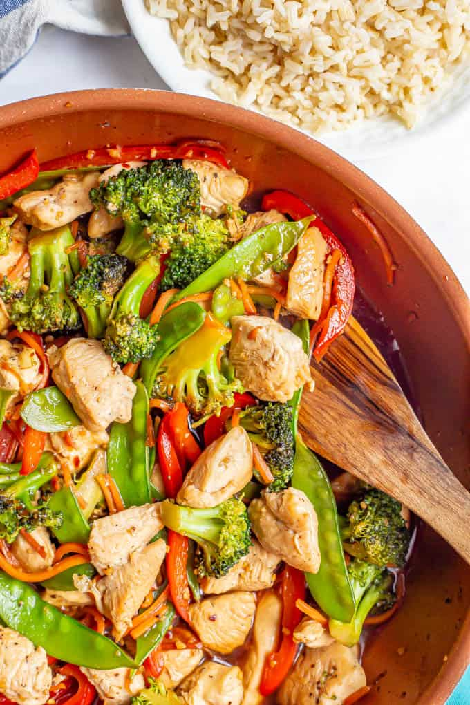 A skillet close-up of chicken and veggies stir fried with a wooden spoon scooping some out and a bowl of rice nearby