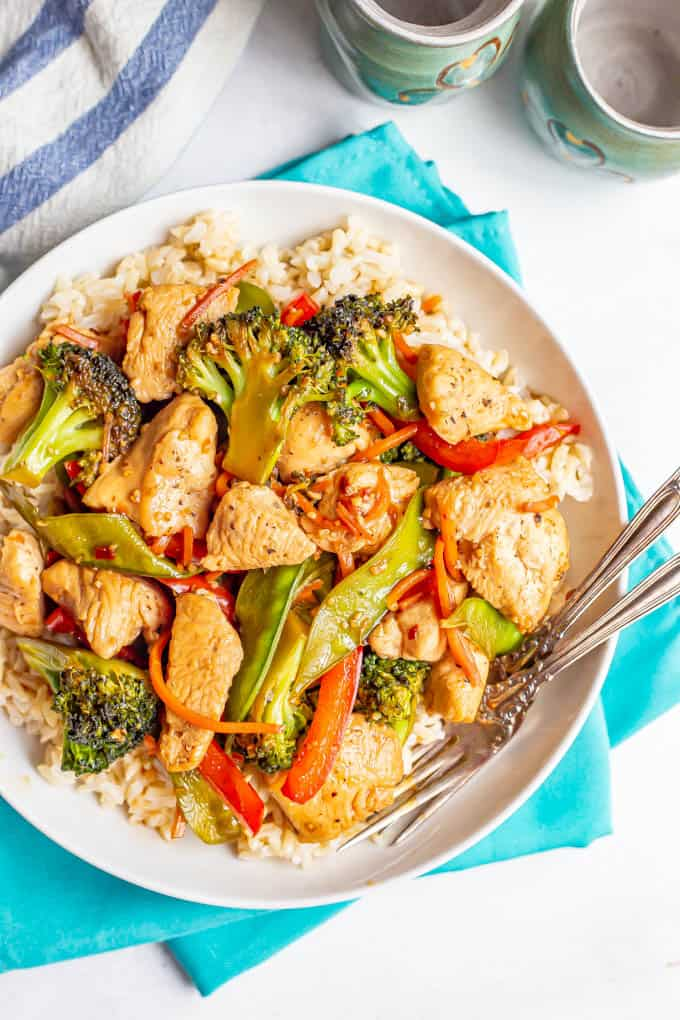 Overhead shot of a large white serving bowl with rice and honey garlic chicken stir fry