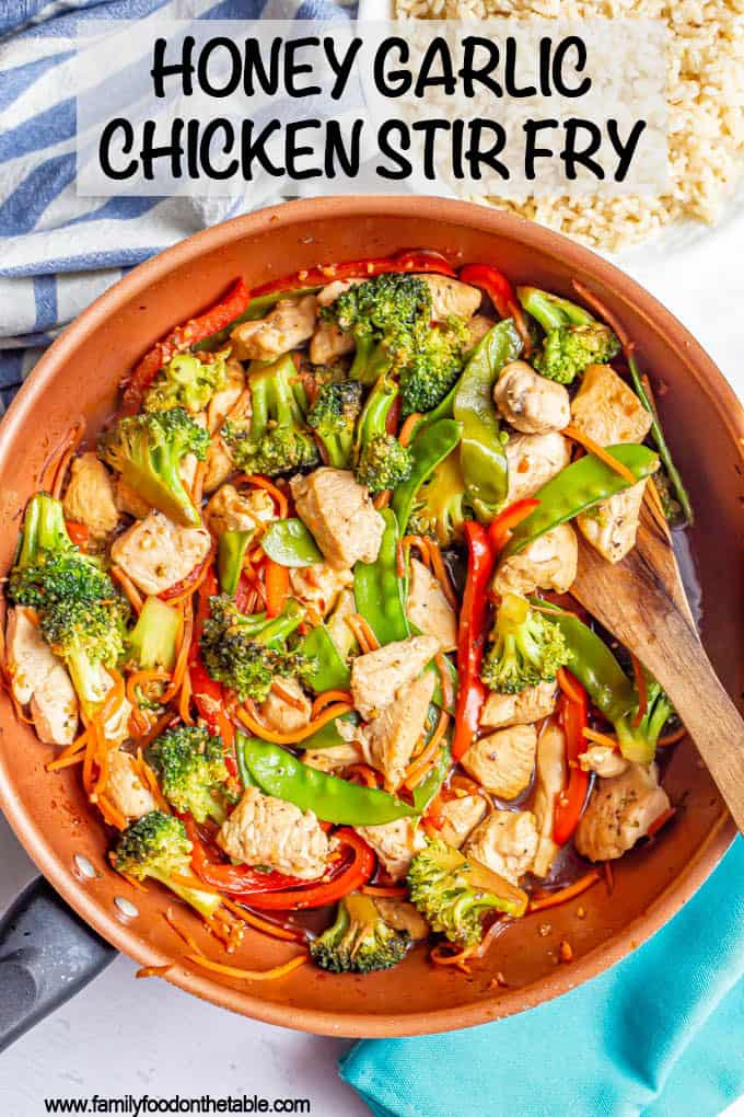 Chicken and vegetable stir fry with honey garlic sauce in a large saute pan with a wooden spoon resting in it