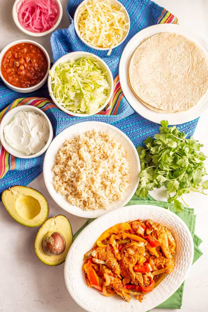 A spread of chicken fajitas with tons of toppings and sides laid out in separate bowls