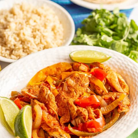 Chicken and bell pepper fajitas in a white serving bowl with lime wedges and a bowl of rice in the background