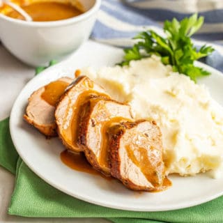 Sliced pork with gravy on a white plate with mashed potatoes and parsley
