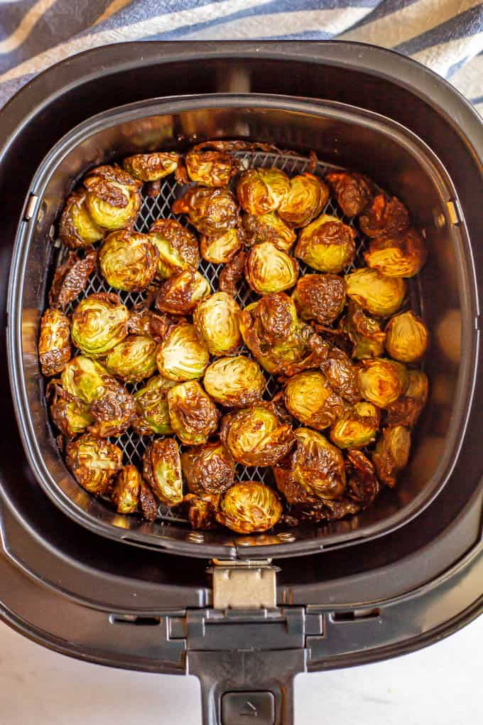Cooked halved Brussels sprouts in the insert of an air fryer