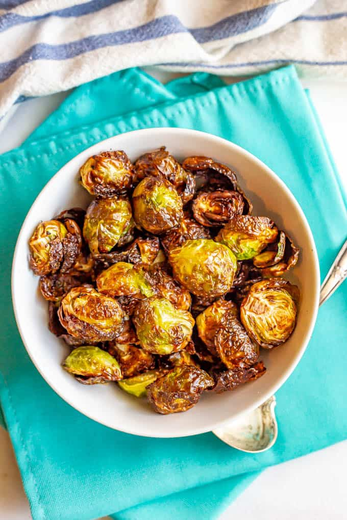 Crispy Brussels sprouts served in a white bowl on turquoise napkins