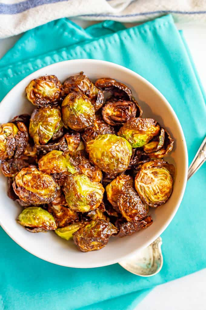 Cooked crispy Brussels sprouts served in a white bowl on turquoise napkins