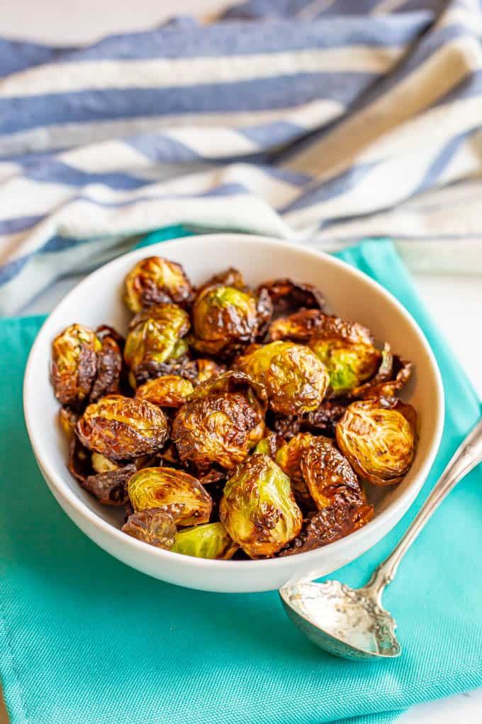 Crispy Air Fryer Brussels sprouts served in a white bowl on turquoise napkins