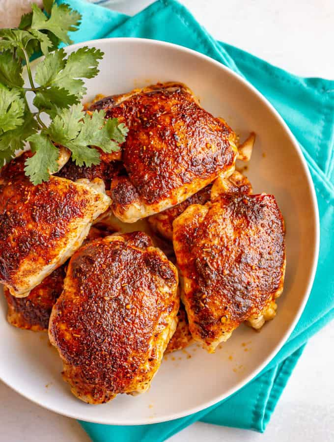 Roasted chicken thighs in a large white bowl set on turquoise napkins