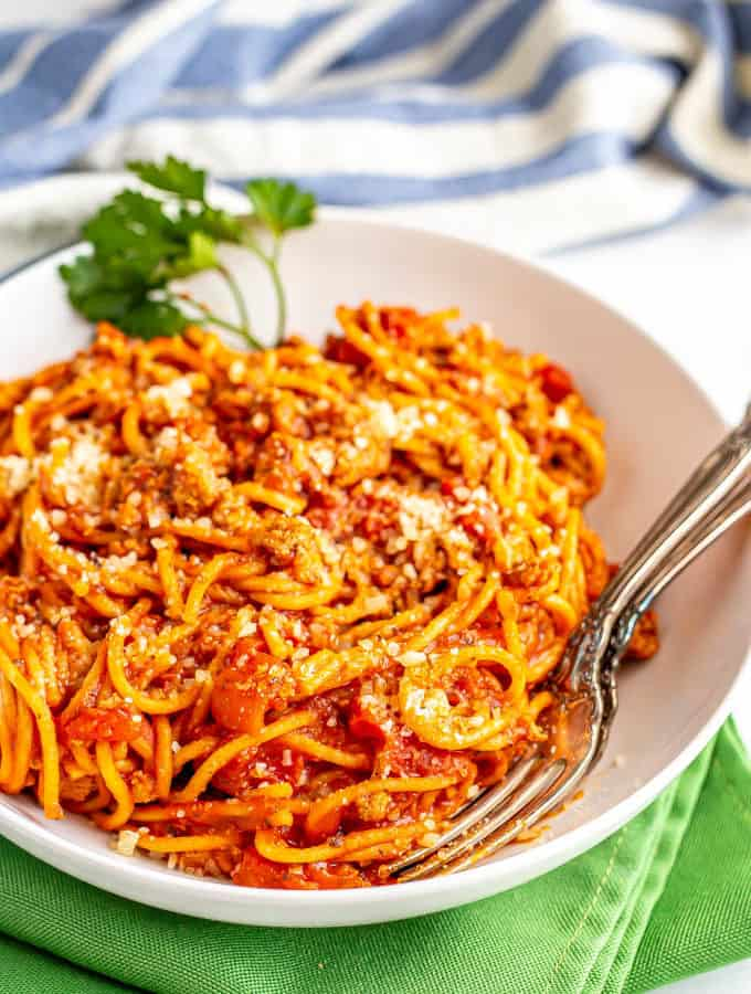 Spaghetti noodles with a meaty tomato sauce in a bowl with two forks tucked in