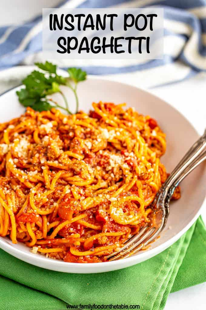A bowl of spaghetti with two forks tucked inside and a text box on top of the photo