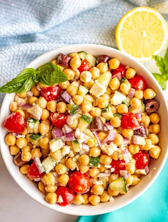 A large white serving bowl with a colorful, fresh Mediterranean style chickpea salad with a cut lemon and basil nearby