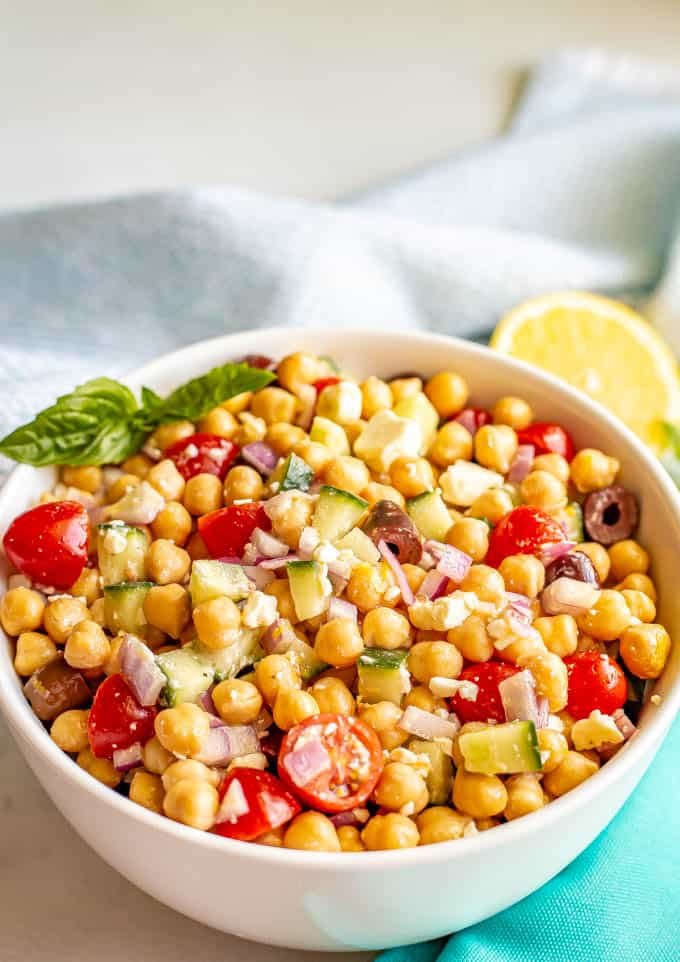 Chickpeas and veggies mixed with a dressing and served in a large bowl