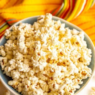 Microwave popped popcorn served in a large blue and white bowl with popcorn scattered on the table and a yellow hand towel