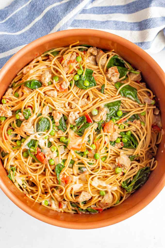 A large copper pot filled with spaghetti noodles, chicken sausage, spinach and peas