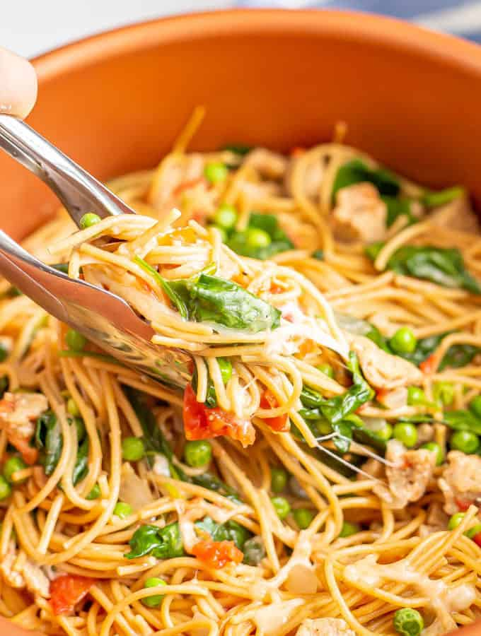 Tongs picking up a scoop of spaghetti noodles with chicken sausage, spinach and peas from a large copper pot