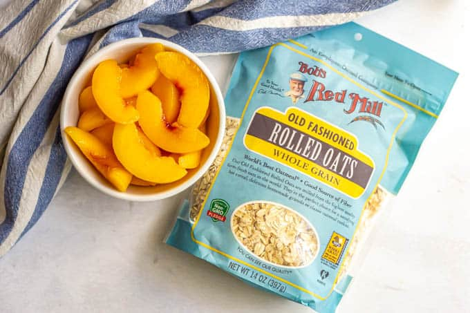 A bowl of sliced peaches and a bag of Bob's Red Mill oats on a counter