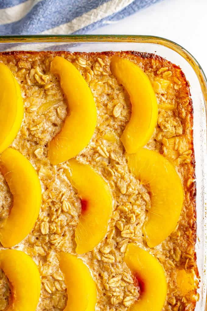 A close up of a baked oat breakfast dish with peach slices on top