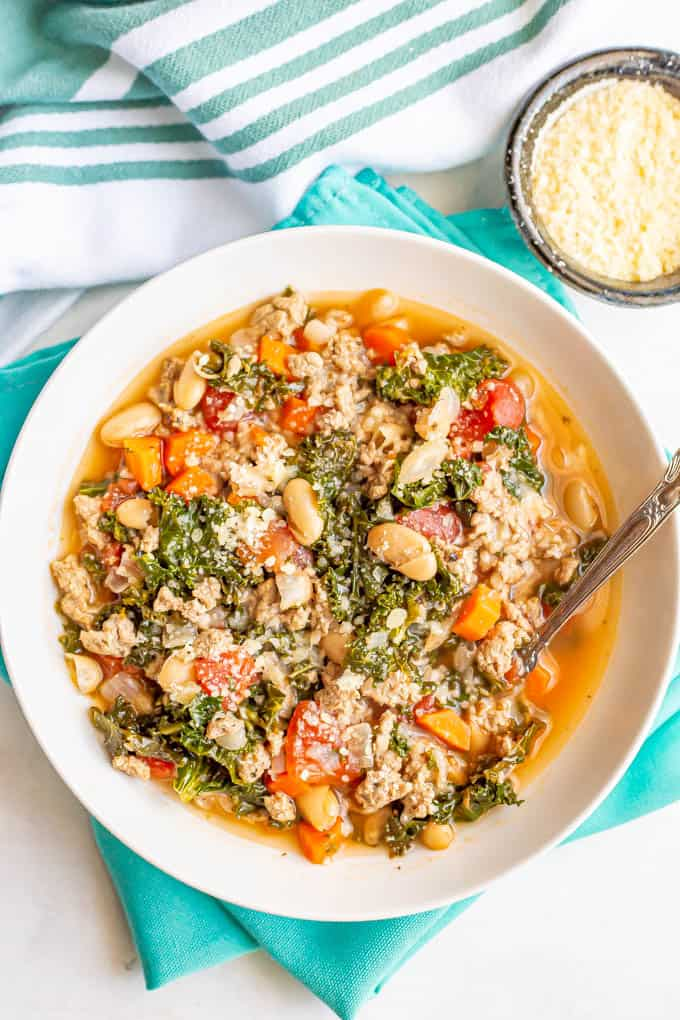 Kale turkey soup with white beans and veggies served with a spoon and a bowl of Parmesan
