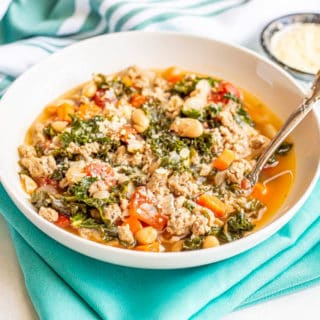 Turkey, bean and kale soup served with Parmesan cheese in a large white bowl