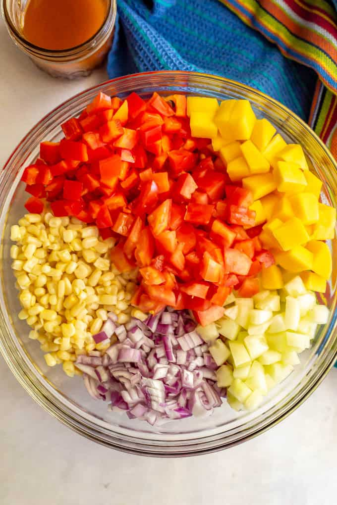 Fresh veggies arranged in a large clear glass bowl before being mixed with a jar of dressing nearby