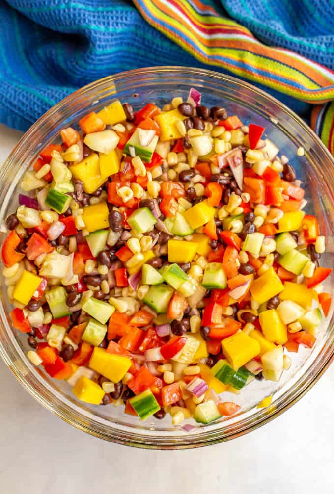 Black bean mango salad with fresh veggies served in a large clear glass bowl