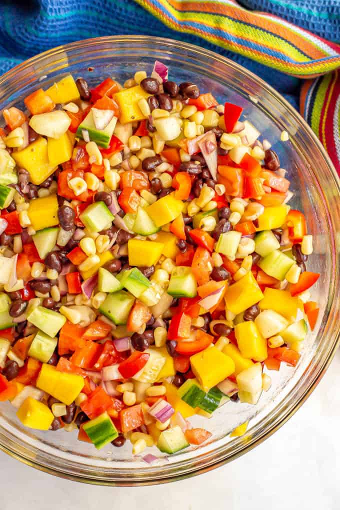Black bean mango salad with fresh veggies in a large clear glass bowl