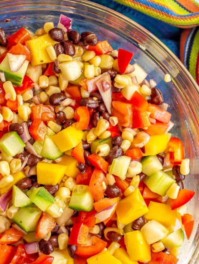 Close up of a colorful veggie mix with black beans and mango in a clear glass bowl
