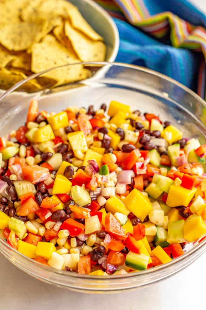 Black bean salad in a large clear bowl with mango, cucumber, corn, tomatoes and peppers