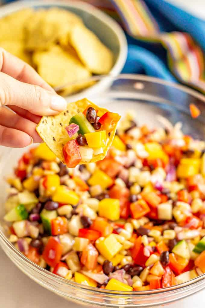 A chip scooping up a black bean and mango salsa