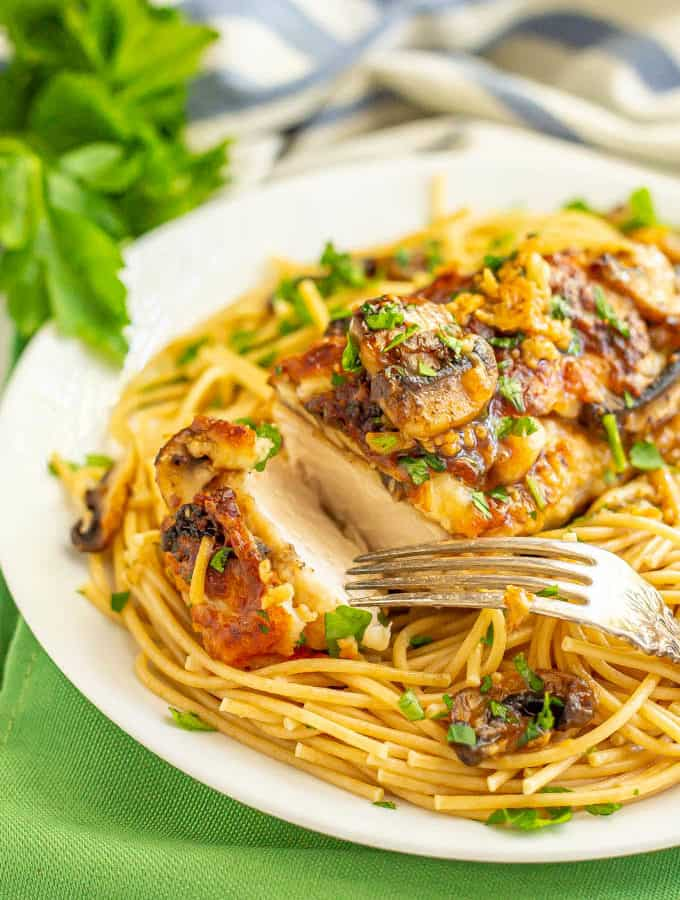 Roasted chicken with mushrooms, cheese and wine sauce over spaghetti noodles on a plate with a fork about to pick up a piece