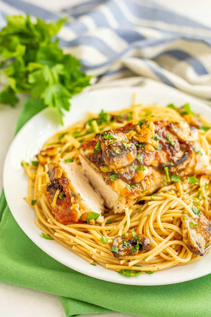 Roasted chicken with mushrooms, cheese and wine sauce over spaghetti noodles served on a white plate
