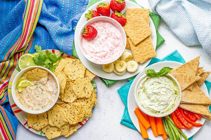 Three bowls with different Greek yogurt dips arranged on plates with various fruit, veggies and other dippers