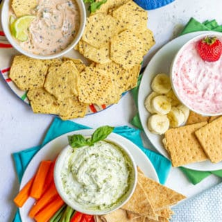 Three bowls with different Greek yogurt dips arranged on plates with various fruit, veggies and other dippers for snacking